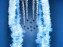 Formation of military training jet aircraft - aerobatic team. Aerobatic team on clear blue sky. Hawk training aircraft in arrow formation making a loop royalty free stock photography
