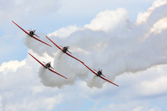 Aerobatic team performs during Oshkosh AirVenture 2013. Oshkosh, WI, USA - August 2, 2013: The AeroShell Aerobatic Team performing during the EAA AirVenture fly Royalty Free Stock Photography