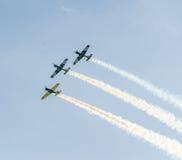 Aerobaticpiloten die in de hemel van de Stad van Boekarest, Roemenië opleiden Gekleurd vliegtuig met spoorrook Royalty-vrije Stock Afbeelding