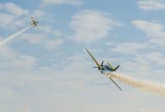 Aerobaticpiloten die in de hemel van de Stad van Boekarest, Roemenië opleiden Gekleurd vliegtuig met spoorrook Royalty-vrije Stock Foto
