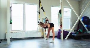 Aerobe Zeit für eine junge Dame in einem leuchtenden ausgerüsteten Studio, das ihren Körper verwendet eine Übung der Bügel TRX, u