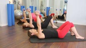 Aerober persönlicher Trainer Pilates in einer Turnhallengruppenklasse
