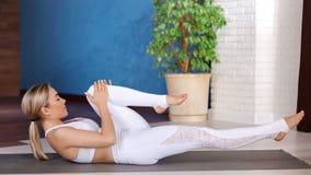 Aerobes flexibles junges Mädchen, das das Lügen auf Matte am vollen Schuss des modernen Yogastudios ausbildend genießt stock footage