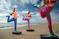 Aerobic on the beach. Fitness, training, aerobics and people concept - group of girls working out with steppers on the beach (Fokus on front female body Royalty Free Stock Images
