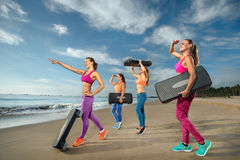 Aerobic on the beach. Fitness, training, aerobics and people concept - group of girls working out with steppers on the beach (Fokus on front female body Royalty Free Stock Photography