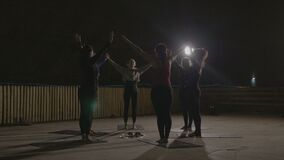 Aerobic class stretching led by a woman instructor in a dark underground cold place illuminated by lamps -. Aerobic class stretching led by a woman instructor in stock video footage