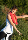 Aerobic Dance/Yoga in the Park. A beautiful young woman exercising in the park with a towel around her neck Royalty Free Stock Images