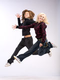 Aerobic dual jumping. Jump of two women with long hair Stock Images