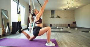 In a aerobic performance studio young lady stretching the body using a elastic bands TRX to get more fit and feeling stock video footage