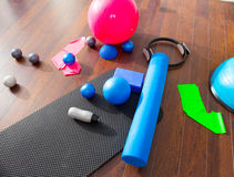 Aerobic Pilates stuff mat balls roller magic ring. Aerobic Pilates stuff like mat balls roller magic ring rubber bands on wooden floor Stock Image