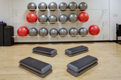 Aerobic steps gym. Step aerobic equipment along with silver and red exercise balls as seen in a club or gym stock image