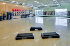 Aerobic steps in gym. Step aerobic equipment along with silver and red exercise balls as seen in a club or gym Stock Photos