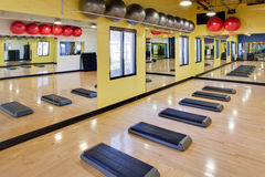 Aerobic steps in gym. Step aerobic equipment along with silver and red exercise balls as seen in a club or gym Stock Images
