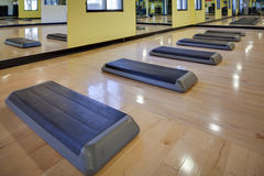 Aerobic steps in gym. Step aerobic equipment along with silver and red exercise balls as seen in a club or gym royalty free stock photography