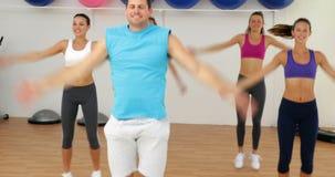 Aerobiclehrer, der eine glückliche Klasse Frauen führt Stockfoto