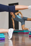 Aerobics. Image of a young woman doing fitness, interestingly framed by another person's legs royalty free stock images