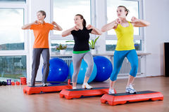 Aerobics. Young women exercising in a step aerobics class royalty free stock photography
