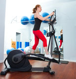 Aerobics cardio training woman on elliptic. Crosstrainer bicycle at gym Royalty Free Stock Images