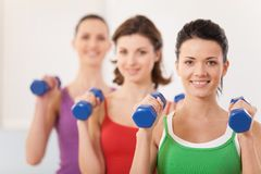 Aerobics class of diverse women of different ages. Girls working out in gym with dumbbells flexing their arm muscles stock photography