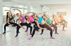 Aerobics class at a gym. With a group of attractive fit young women in colorful sportswear working out in synchronisation, in a wellness, health and fitness royalty free stock photography
