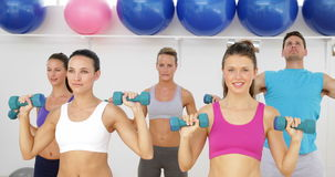 Aerobics class lifting dumbbells together Royalty Free Stock Photos