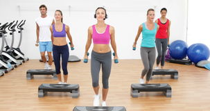 Aerobics class stepping together led by instructor and lifting dumbbells stock video