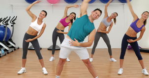 Aerobics class stretching together led by instructor