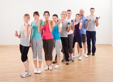 Aerobics class working out with dumbbells. Aerobics class of diverse men and women of different ages working out Royalty Free Stock Photos