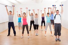 Aerobics class working out with dumbbells. Aerobics class of diverse men and women of different ages working out in a gym with dumbbells flexing their arm Stock Photos
