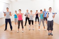 Aerobics class working out with dumbbells. Aerobics class of diverse men and women of different ages working out in a gym with dumbbells flexing their arm Stock Photography