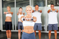 Aerobics with dumbbells. Group of people doing aerobics with dumbbells in gym royalty free stock image