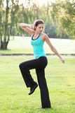 Aerobics outdoor. Young woman practicing aerobics exercise in green meadow stock image