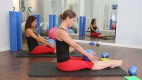 Aerobics pilates women personal trainer with pupil in a row at gym