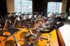 Aerobics spinning exercise bikes gym room in a row. Aerobics spinning exercise bikes gym room with many in a row Royalty Free Stock Photos