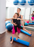 Aerobics woman personal trainer of children girl. Aerobics women personal trainer of children girl stability with foam roller stock photos