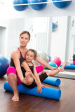 Aerobics woman personal trainer of children girl. Aerobics women personal trainer of children girl stability with foam roller royalty free stock photography
