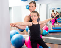 Aerobics woman personal trainer of children girl. Aerobics women personal trainer of children girl stability with foam roller royalty free stock photo