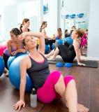 Aerobicspilateskvinnor grupperar att ha en rest på idrottshallen Royaltyfria Foton