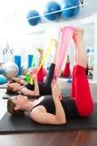 Aerobicspilateskvinnor med rubber band i en rad Royaltyfri Bild