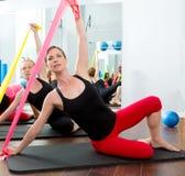 Aerobicspilateskvinnor med rubber band i en rad Royaltyfria Bilder