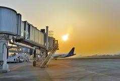 Aerobridge parkte im Flughafen bei Sonnenuntergang Lizenzfreies Stockfoto