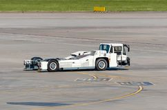 Aerodrome tow tractor is driving along the steering paths at the airport. Aerodrome tow tractor is driving along the steering paths at the airport stock photo
