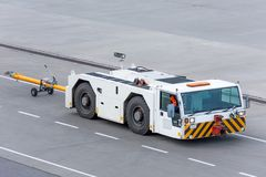 Aerodrome tow tractor is driving along the steering paths at the airport.  stock photography