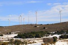Aerogenerator windmills on snow mountain Royalty Free Stock Image