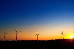 Aerogeneratorwindmühlen auf Sonnenunterganghimmel Stockfotos
