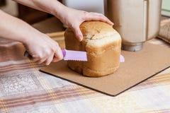 A aeromoça corta o naco de pão com faca grande fotos de stock