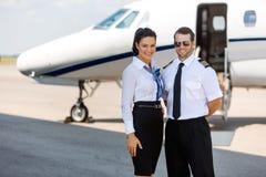 Aeromoça de bordo feliz e piloto Standing Against Imagem de Stock Royalty Free