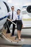 Aeromoça de bordo segura e piloto Standing On Ladder Imagem de Stock