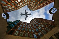 Aeroplane through the buildings royalty free stock photo