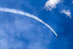 Aeroplane Dive. Arobatic aeroplane dives with a trail of white smoke against a blue sky Royalty Free Stock Photos